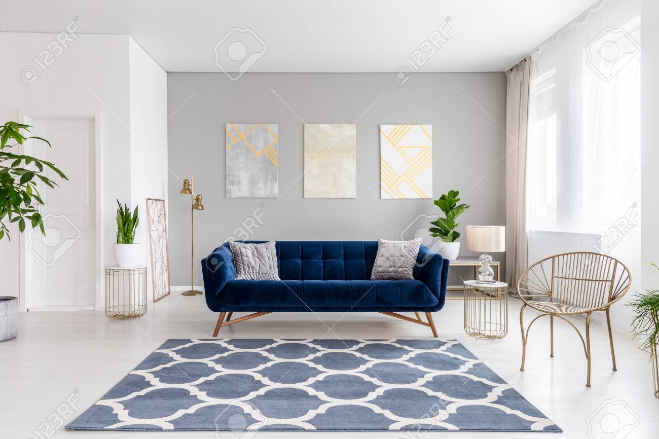 Real photo of bright living room interior with royal blue couch three simple paintings