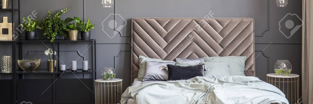 Bed with headboard between gold tables in grey bedroom interior with plants. Real photo - 107096359