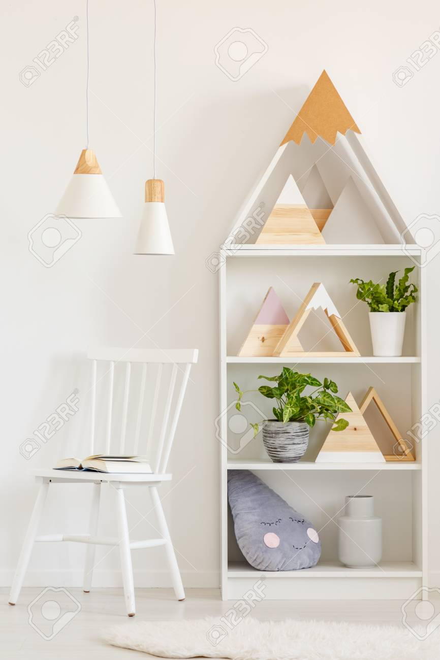 Open Book On A Simple Wooden Chair And A Bookcase With Plants