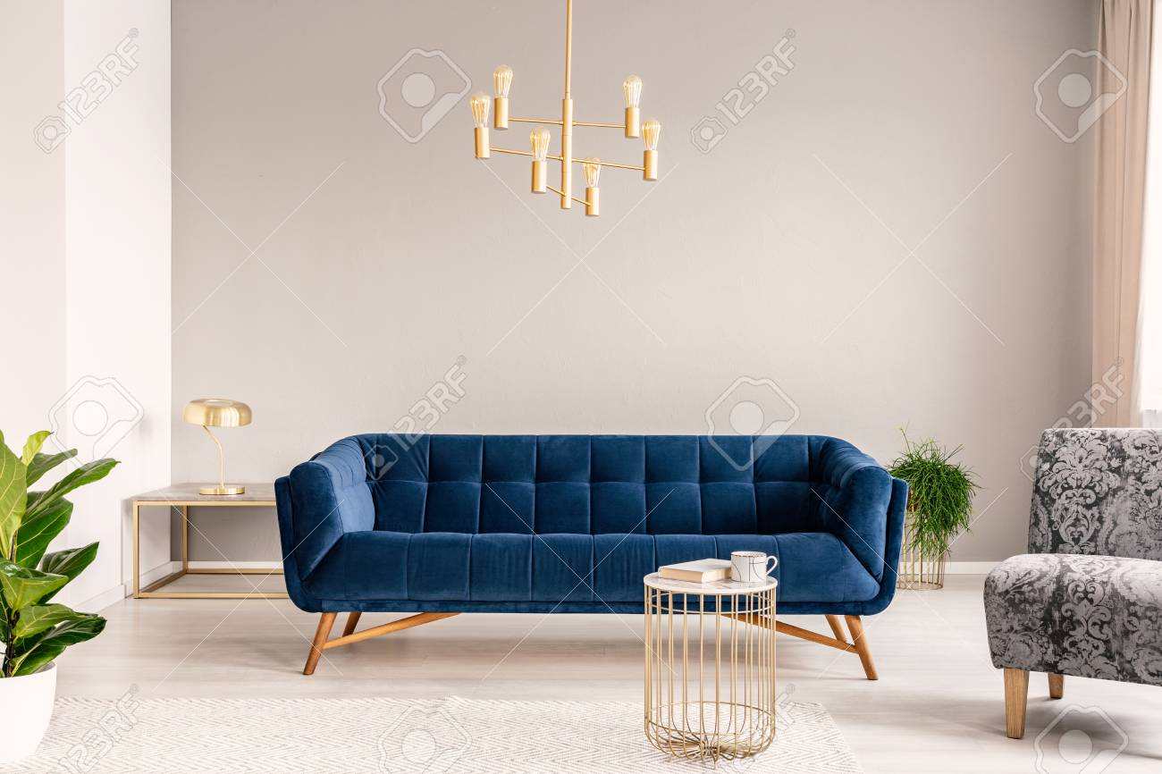 Gold Lamp Hanging Above Royal Blue Sofa In Real Photo Of Light Stock Photo Picture And Royalty Free Image Image 107307695