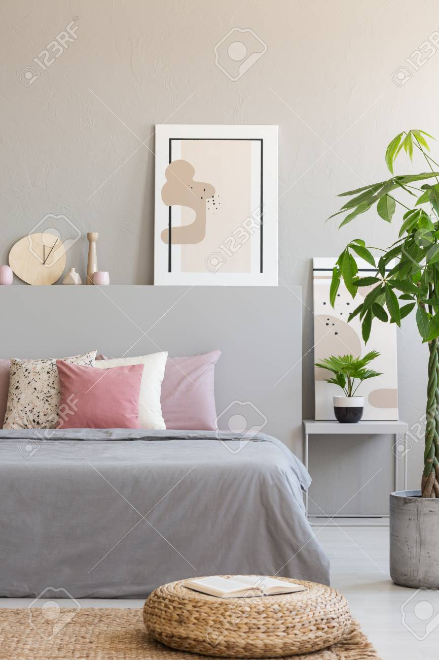 Pouf and plant next to grey bed with pink cushions in bedroom..