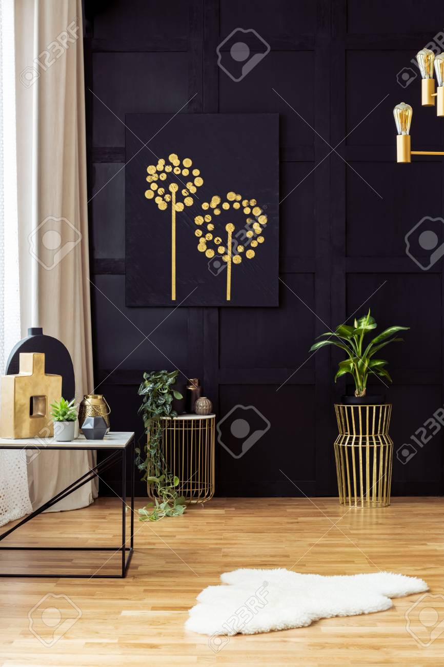 Elegant living room interior with golden accents, painting on..