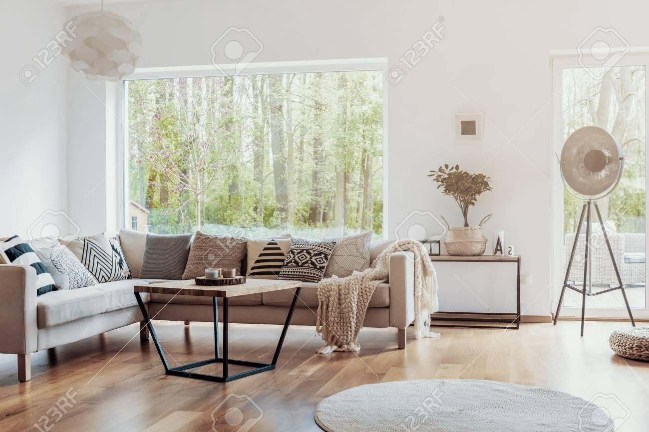 Print pattern pillows on a beige corner sofa by a big glass window..
