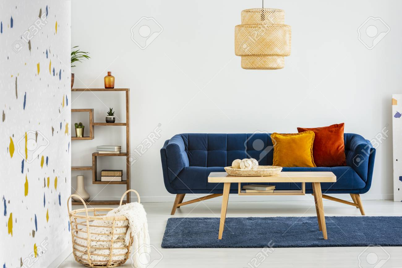 Lamp above wooden table in front of blue sofa with pillows in..