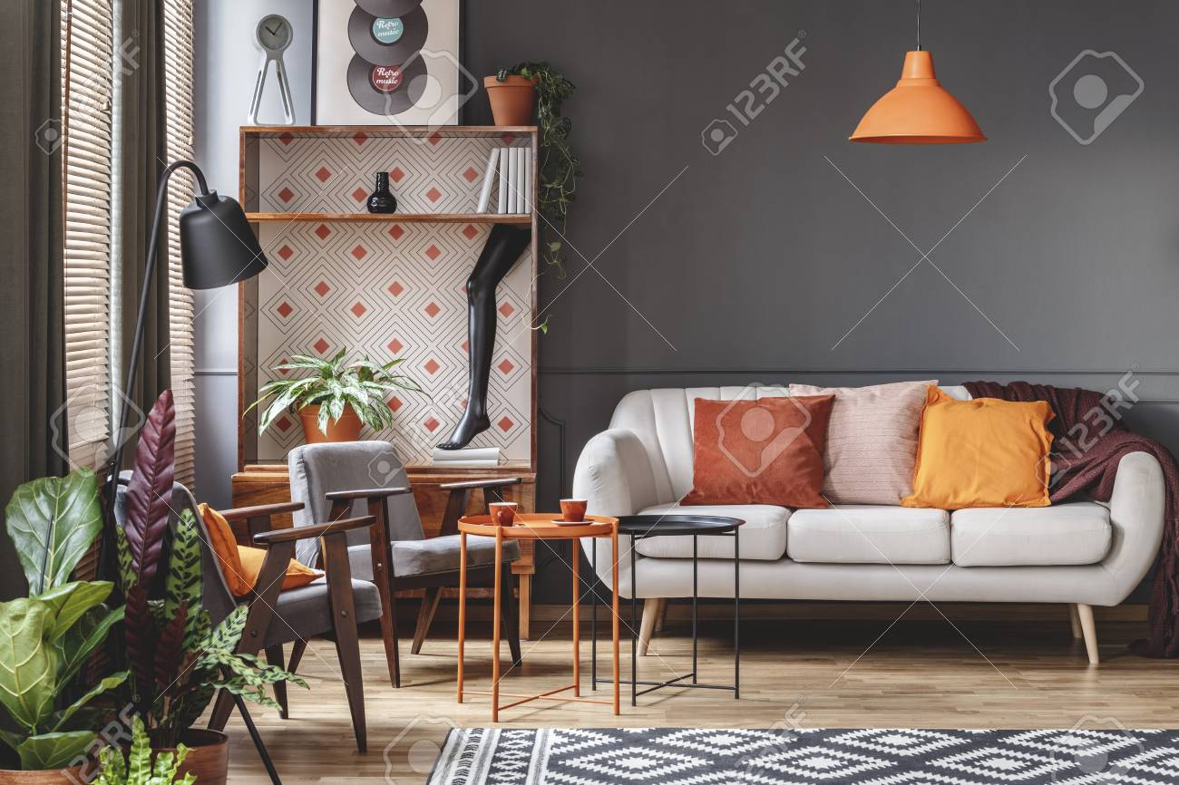 Orange lamp above sofa in vintage living room interior with plants..