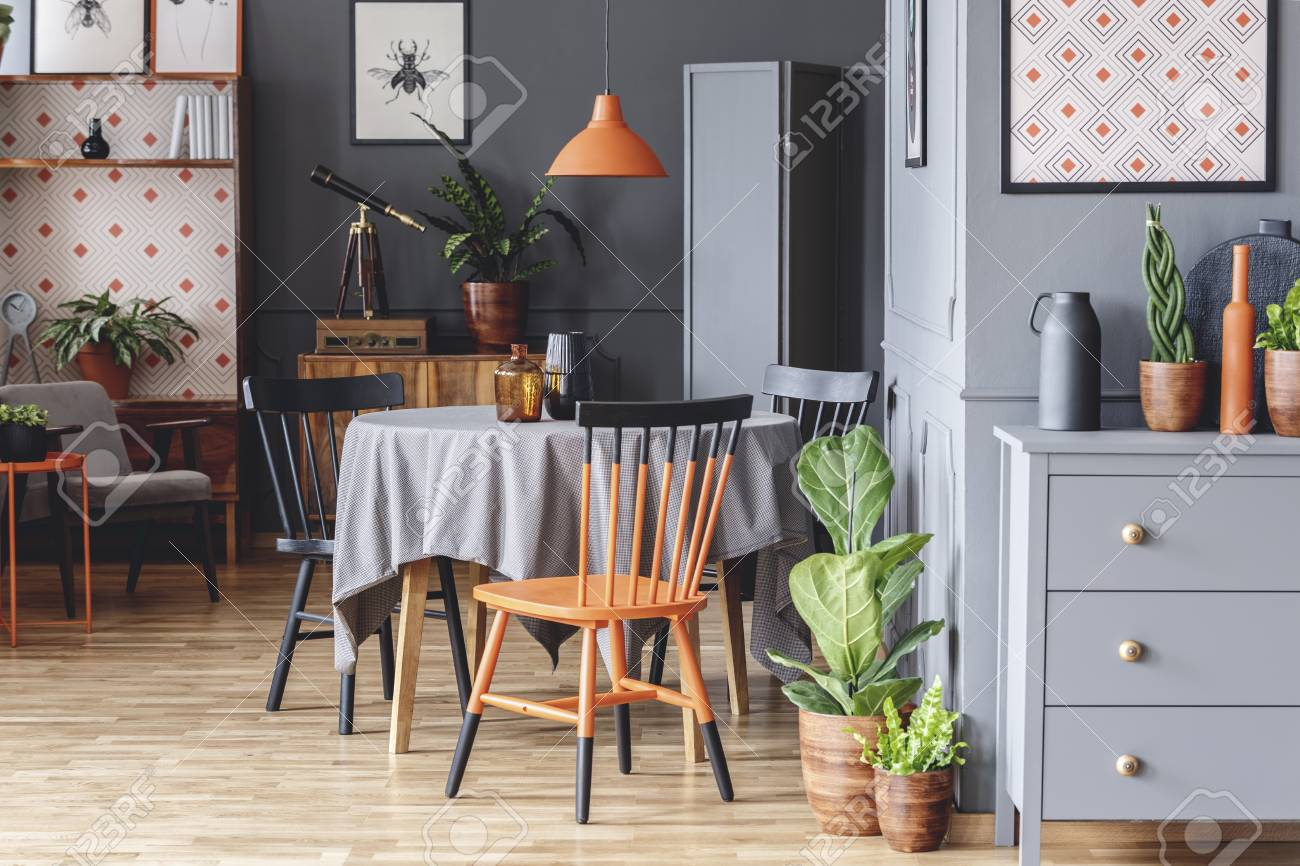 Orange and black chair at table in grey retro dining room interior..
