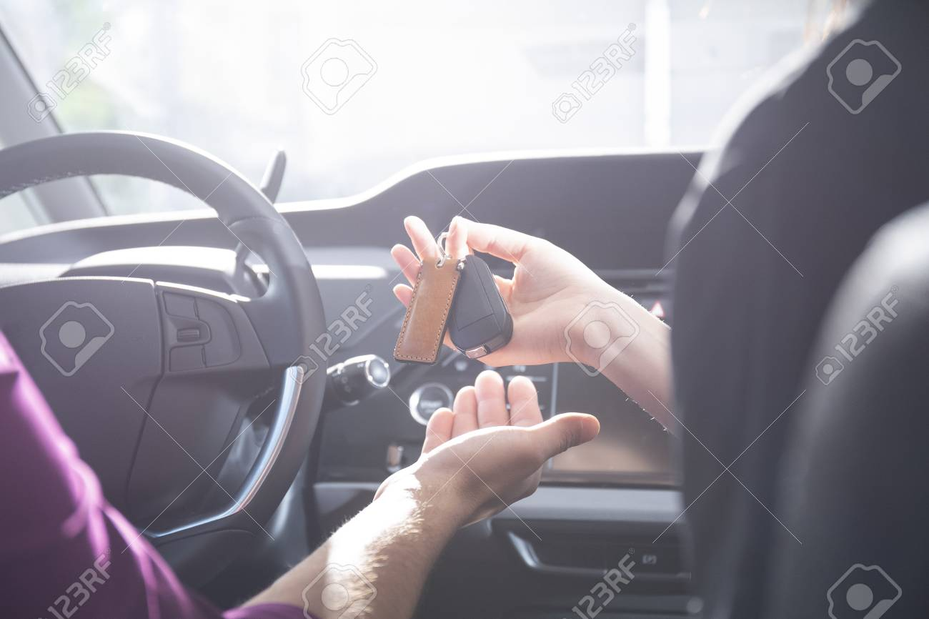 Close Up Of A Hand Giving Car Keys To A Driver Inside The Car Stock