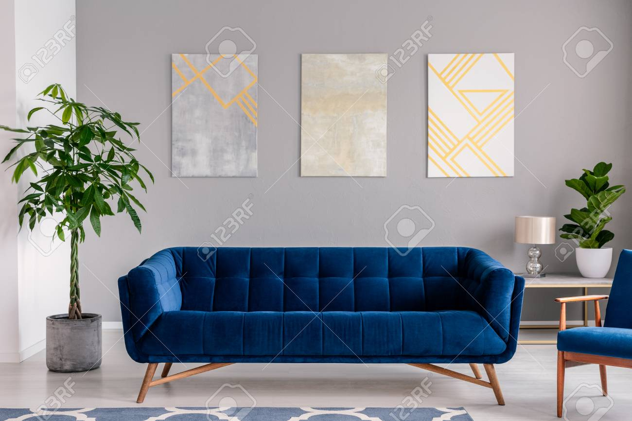 A dark blue velvet couch in front of a gray wall with graphic..