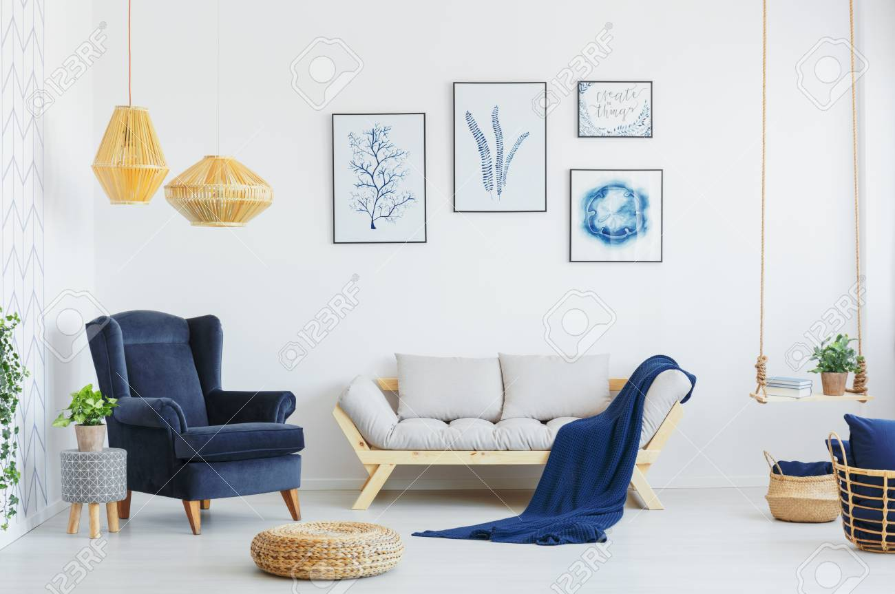 Blue armchair next to a grey sofa, wicker pouf and lamps in a..