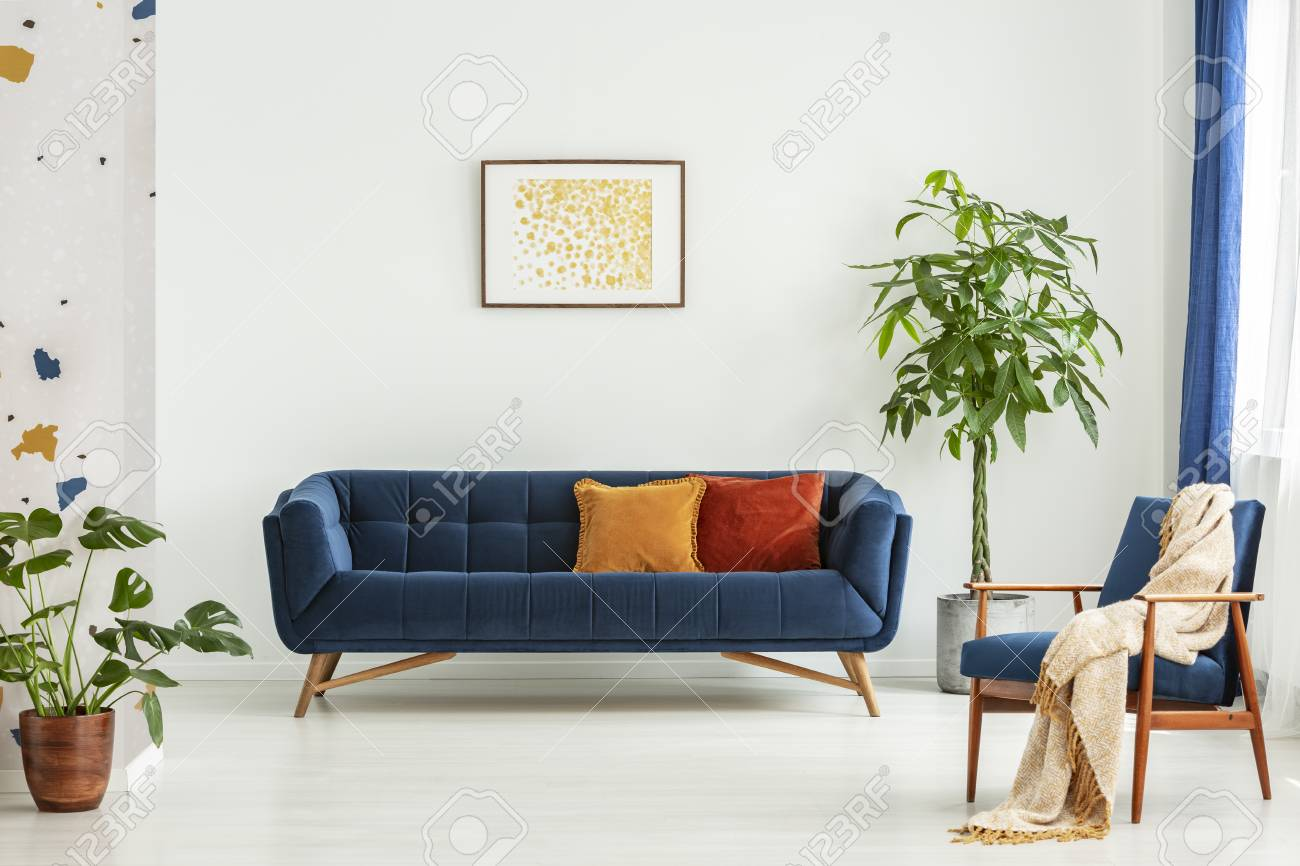 Mid Century Modern Chair With A Blanket And A Large Sofa With