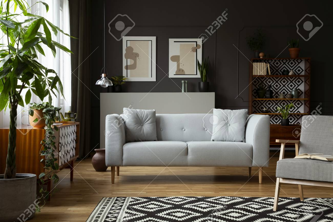 Real photo of dark grey living room interior with posters and..