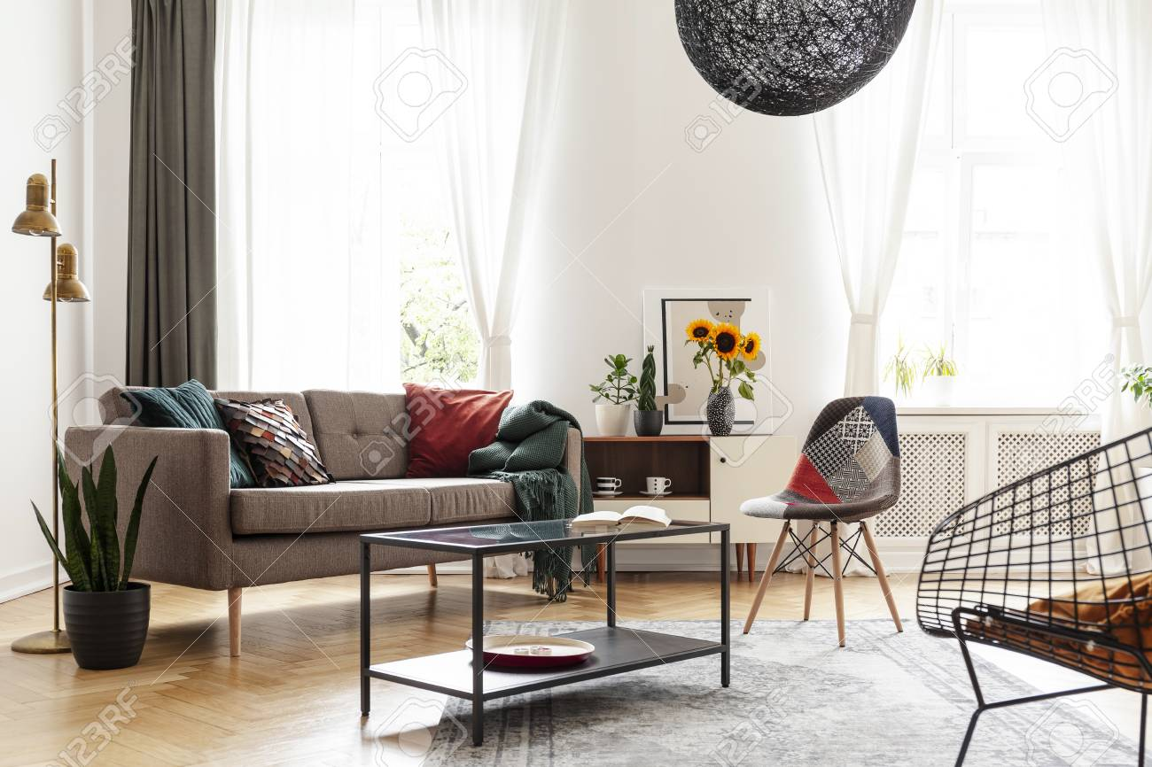 Simple Brown Sofa With Cushions In An Eclectic White Living