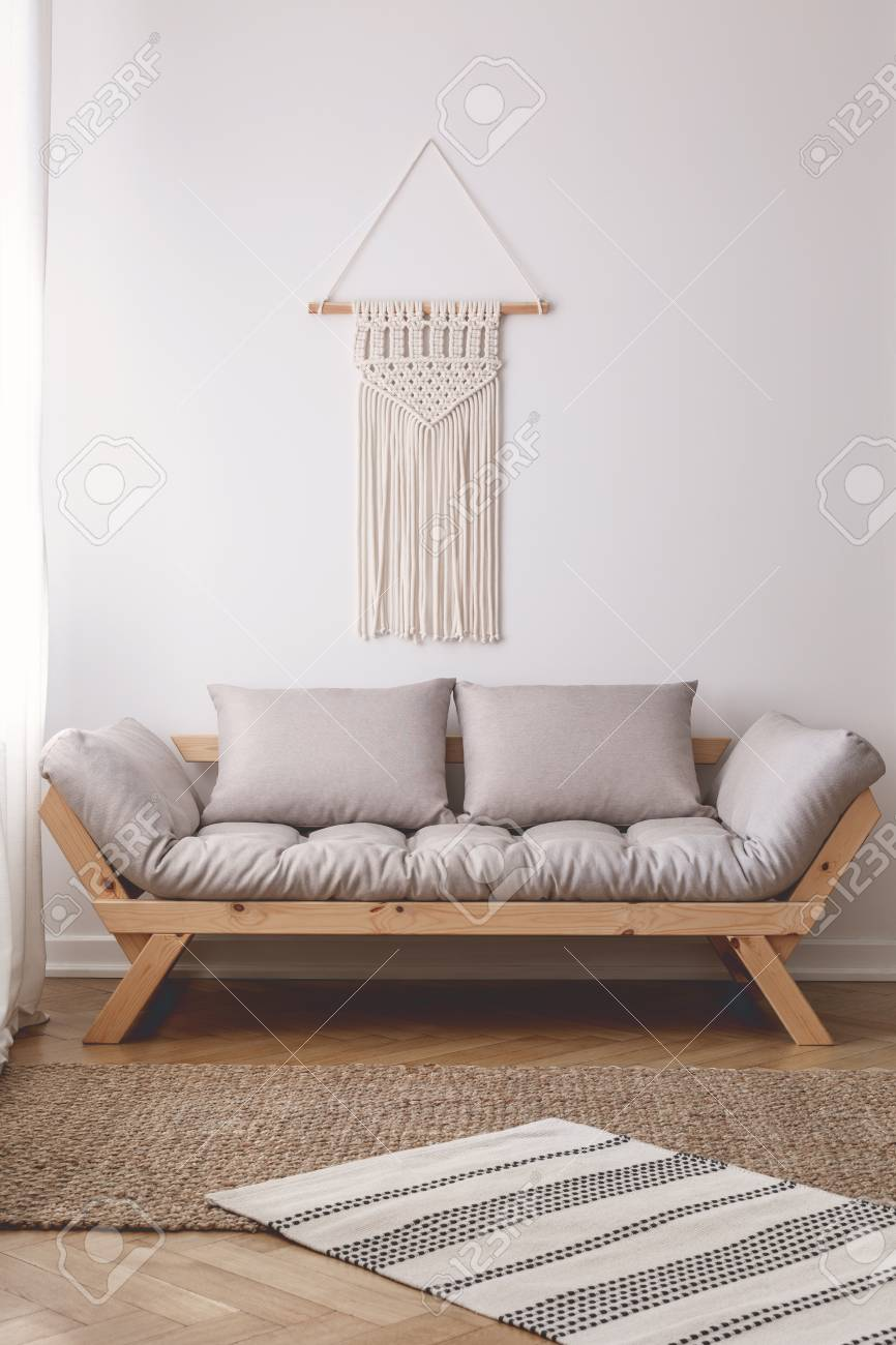 Beige Wooden Couch With Pillows In Simple White Living Room Interior