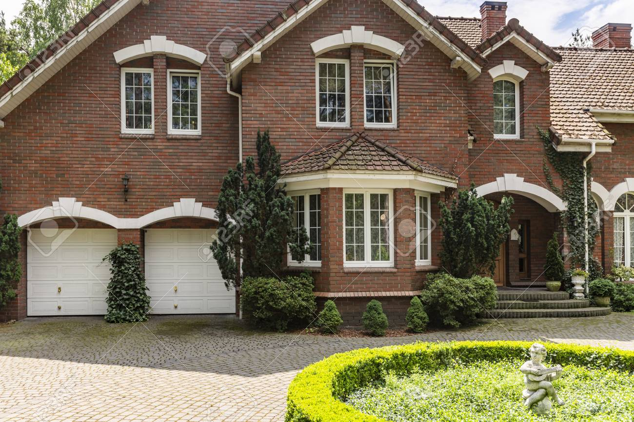 Real photo of a brick house with a bay window, garages and round garden in front of the entrance - 108319899