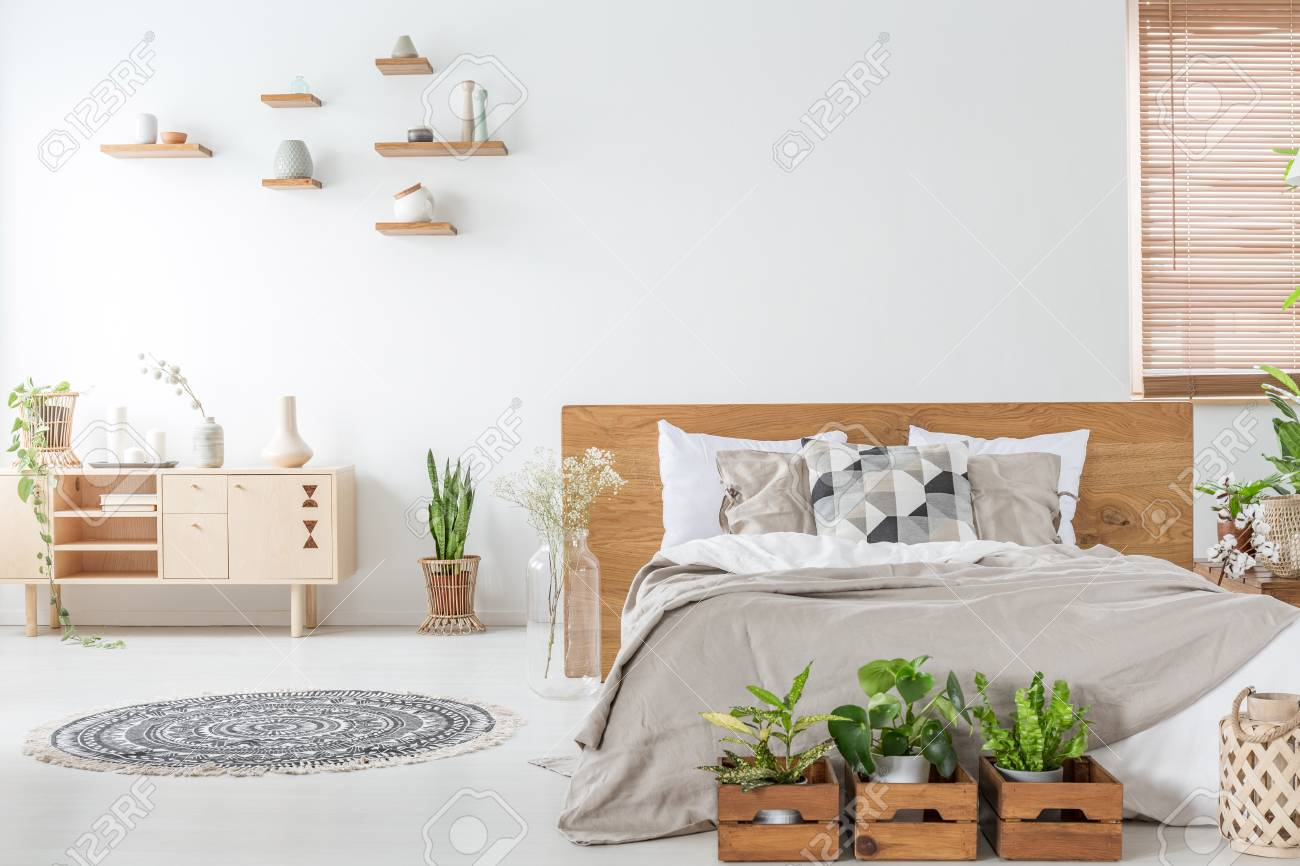 Plants In Front Of Wooden Bed In White Bedroom Interior With Stock Photo Picture And Royalty Free Image Image 108320191