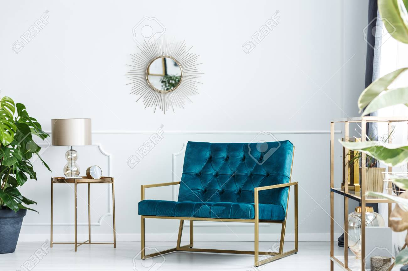 Sunburst mirror on a white wall of a fancy living room interior..