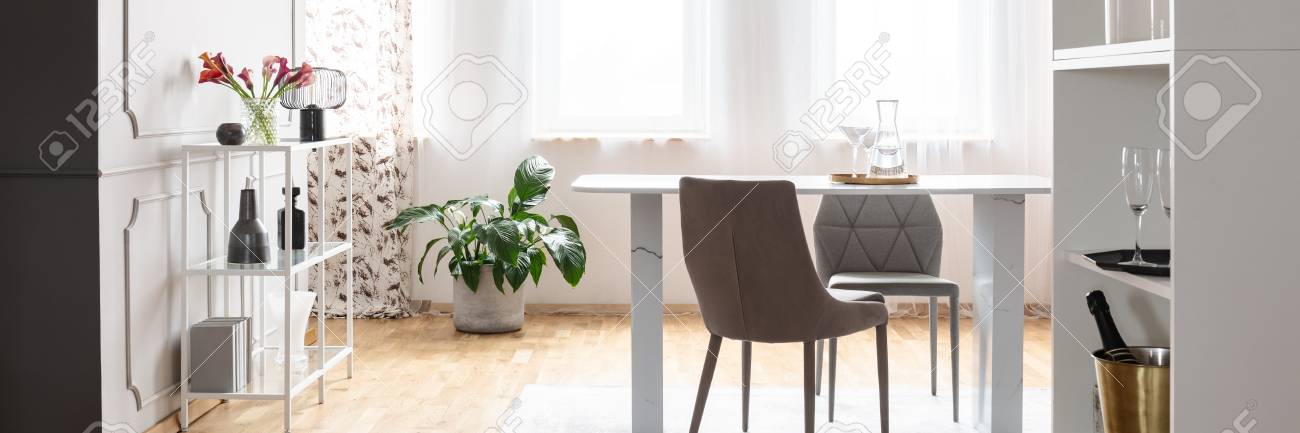 White dining room interior in the real photo with window with..