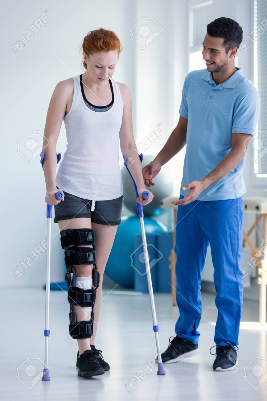 Physiotherapist helping woman with stiffener on the leg walking with crutches - 108810645