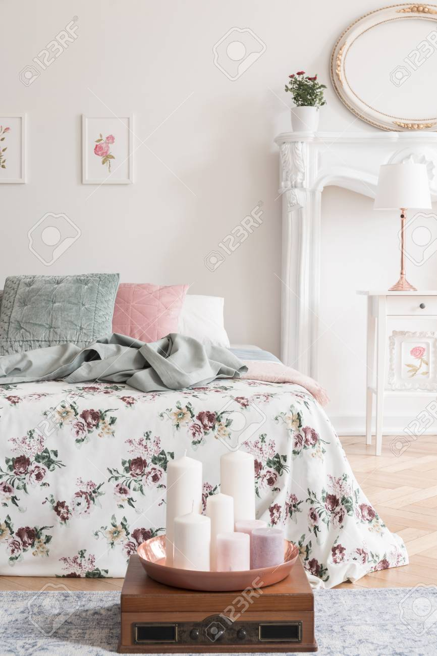 English style bedroom interior with a bed dressed in rose pattern..