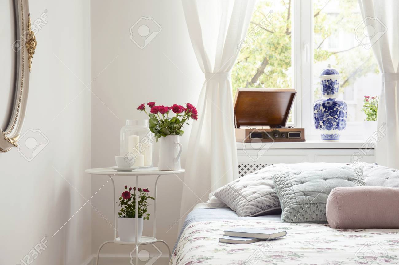 Red roses on table by a bed side in a pastel bedroom interior..