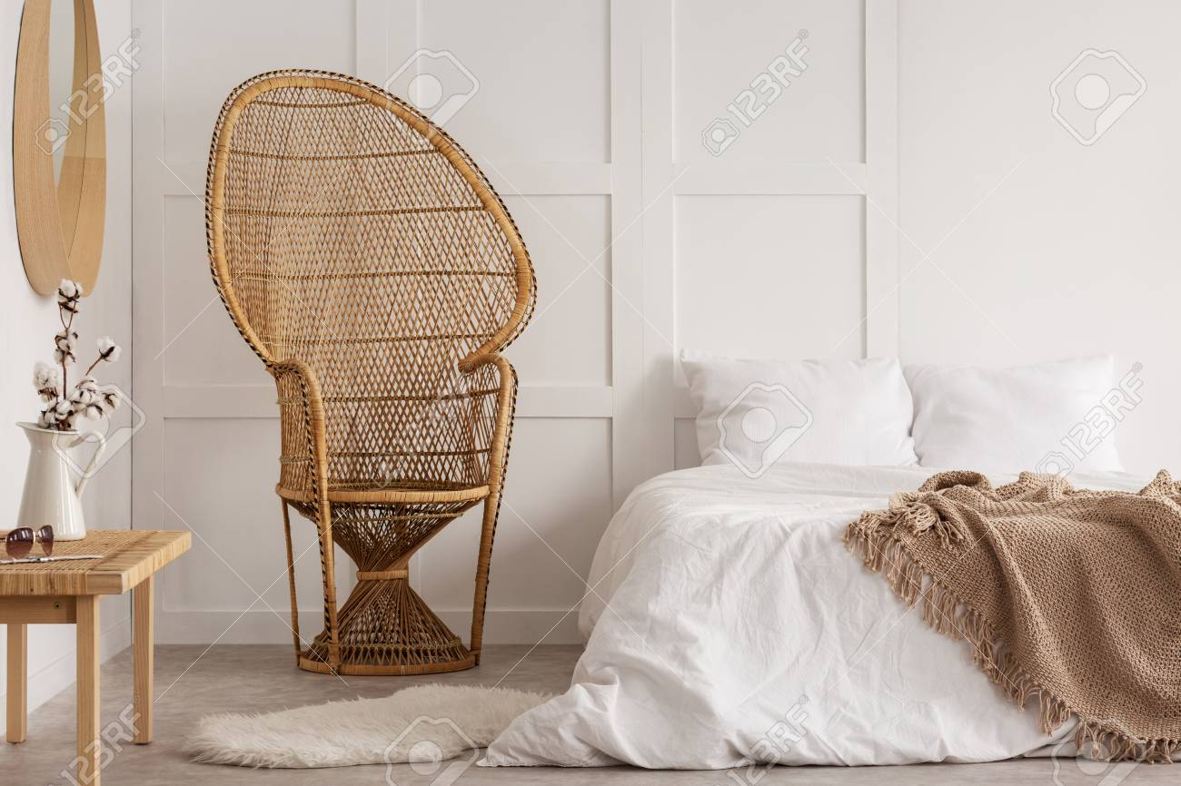 Flowers on wooden table next to rattan chair in white bedroom..