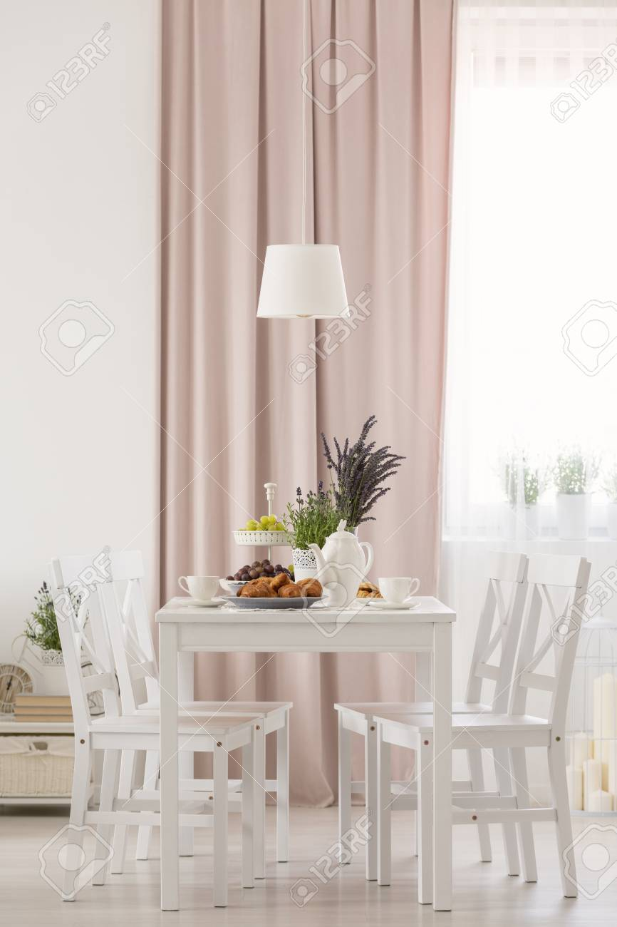 White chairs at table with flowers under lamp in dining room..