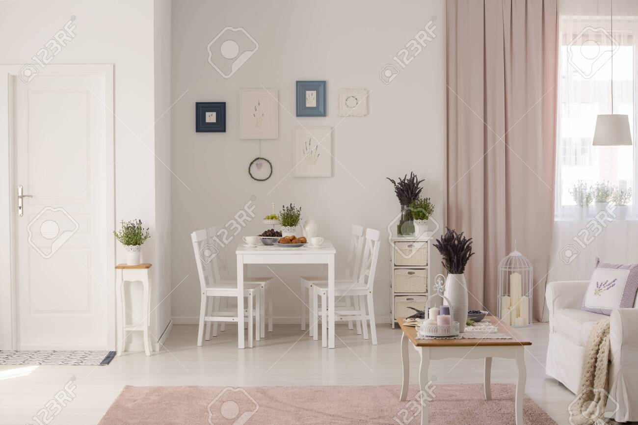 Flowers on table next to sofa in white and pink apartment interior with posters and drapes. Real photo - 109360294