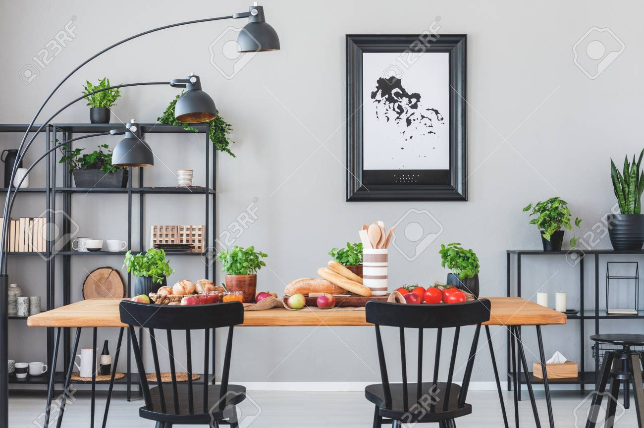 Lamp Above Black Chairs And Wooden Table With Food In Grey Dining Room Interior Poster