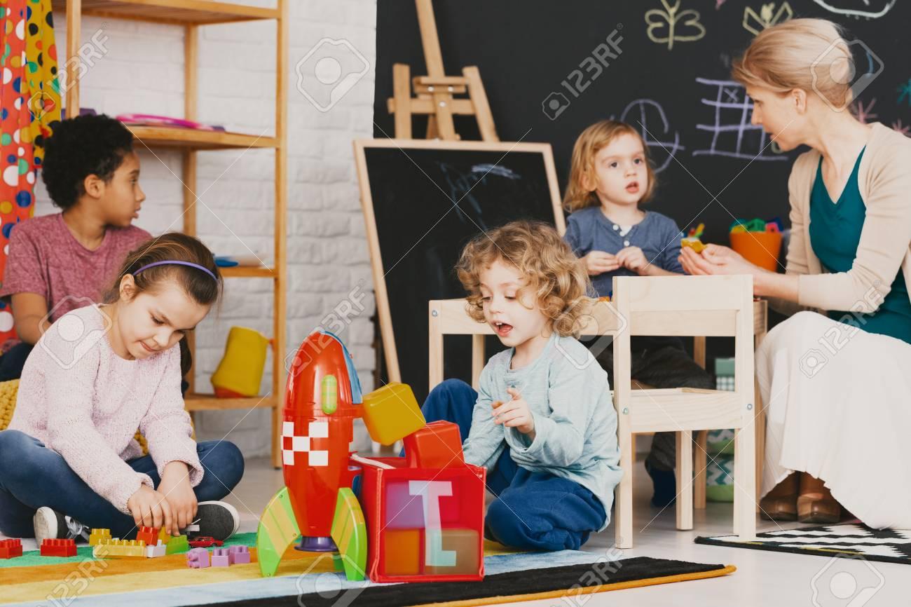 Multicultural kids playing together in kindergarten with big blackboard - 109832549