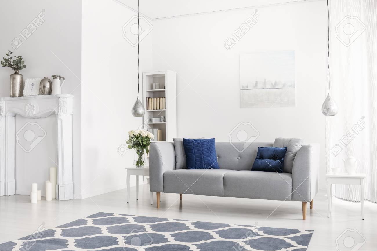 Patterned blue carpet in front of grey sofa in white apartment..