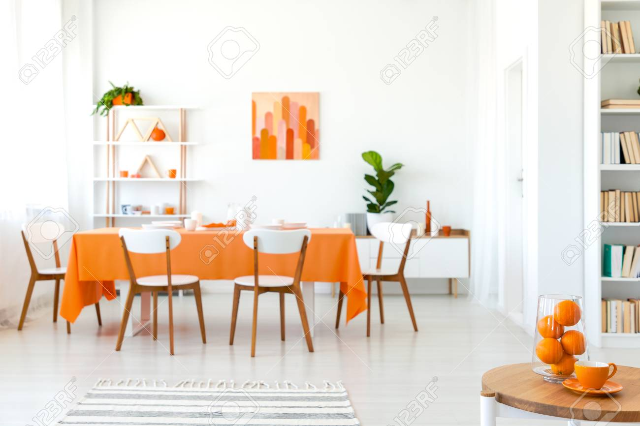 White Chairs At Table With Orange Cloth In Modern Dining Room