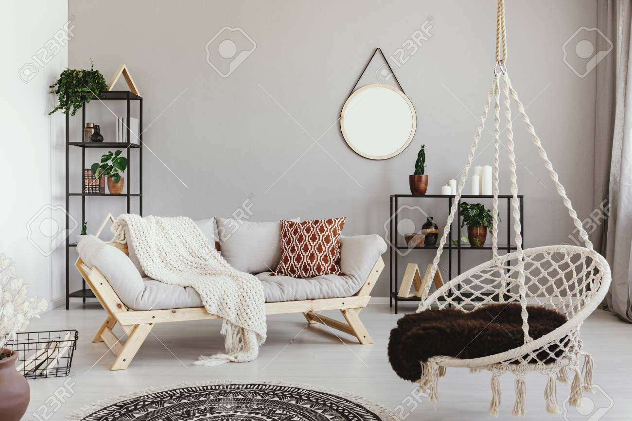 Hanging Chair Near Grey Wooden Sofa In Ethno Living Room Interior