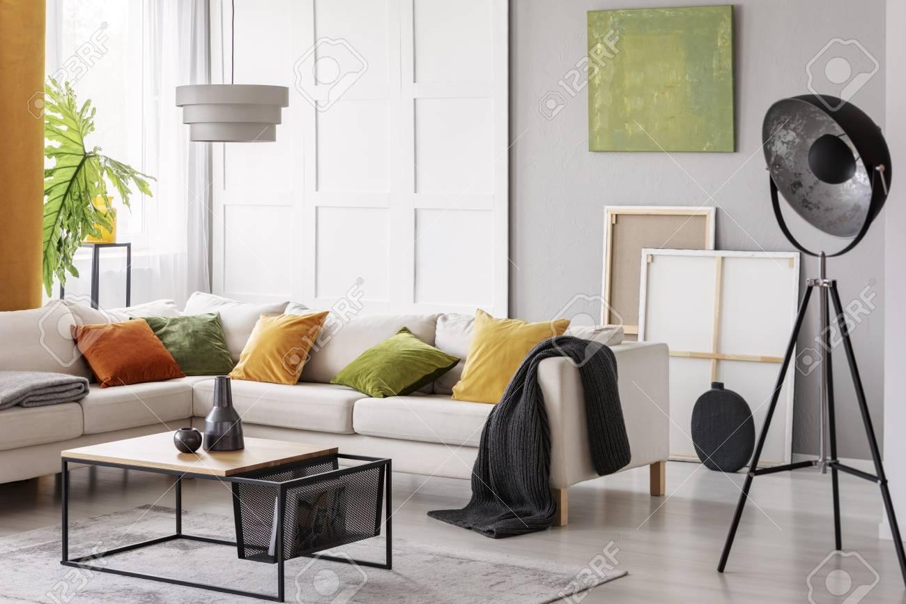 White elegant corner sofa with orange green and yellow pillows..
