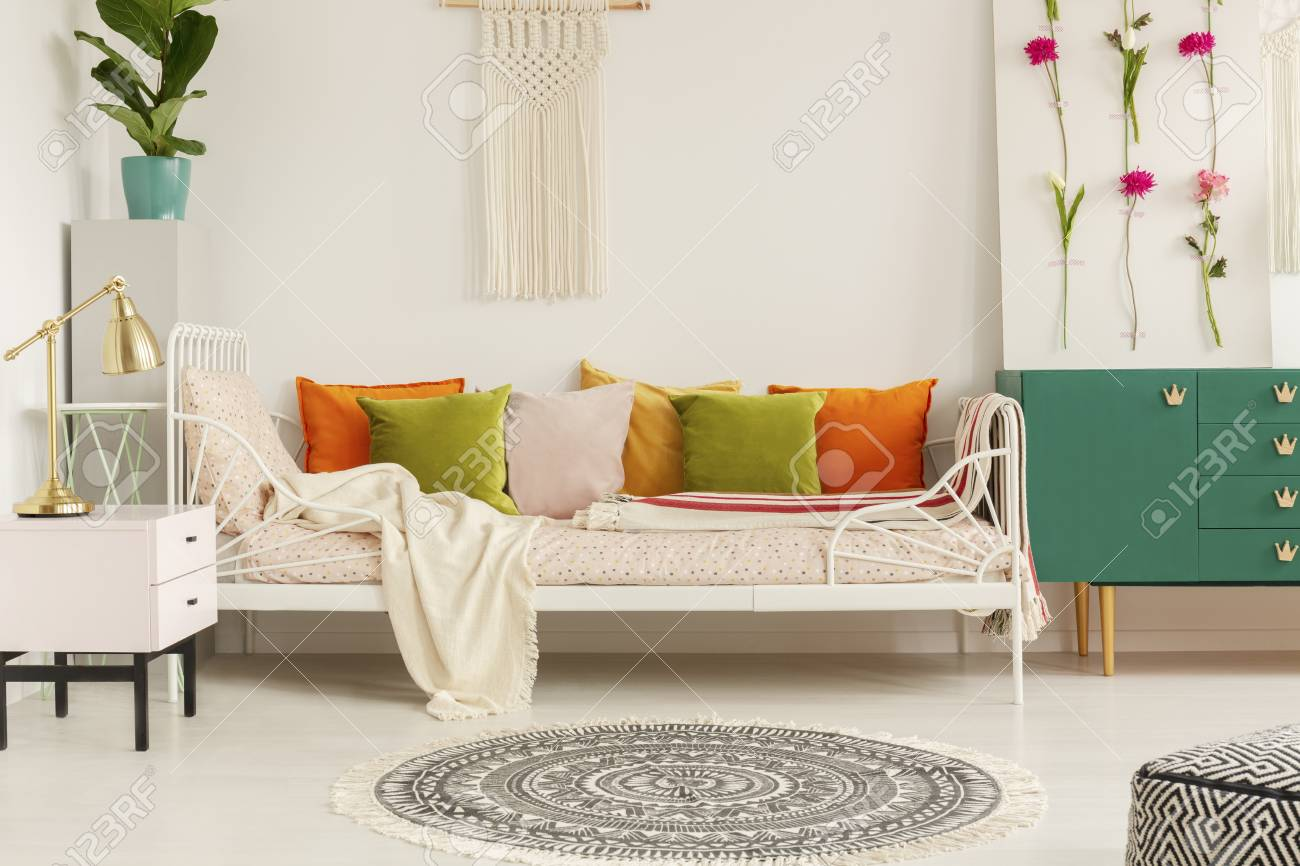 Olive green, orange, yellow and pastel pink pillows on comfortable..