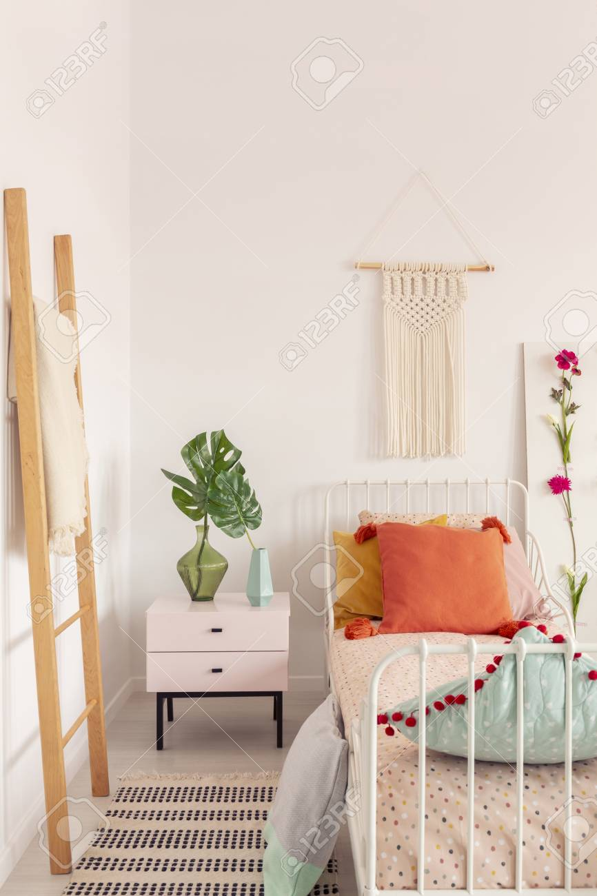 Orange Pillow On Single Metal Bed In Stylish Bedroom Interior