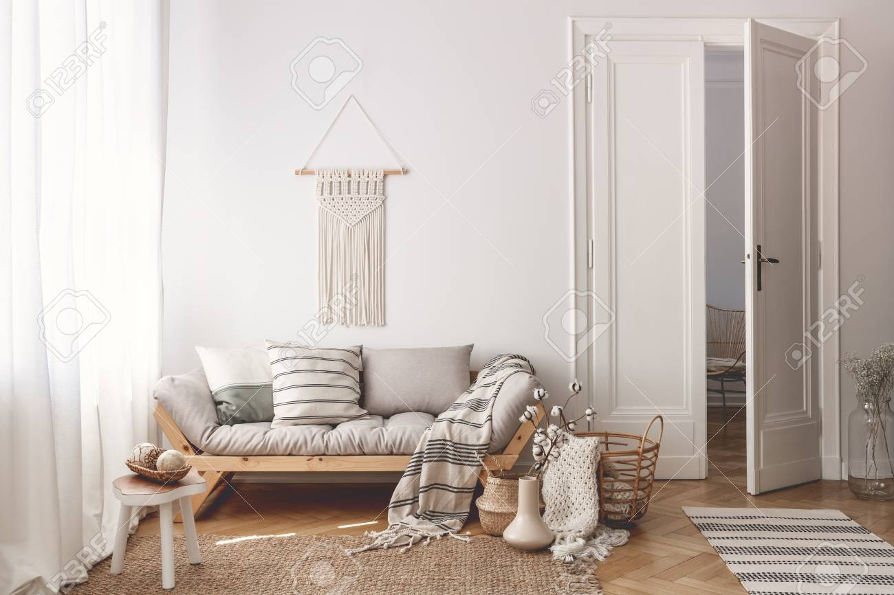 Living Room With Stylish Macrame, Sofa, Wooden Accessories And Doors Open  To Next Room