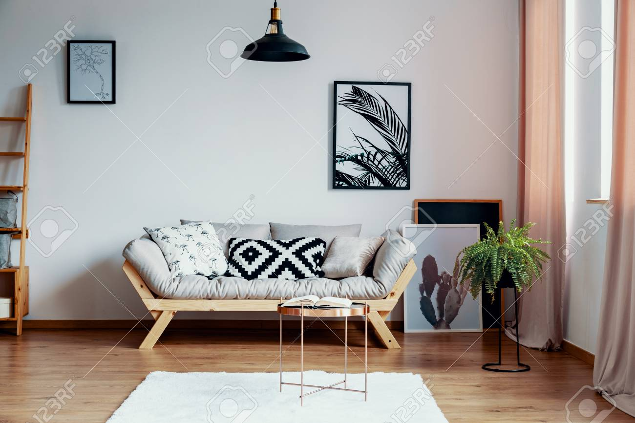 Patterned black and white pillow on beige scandinavian sofa in stylish interior with gallery of poster
