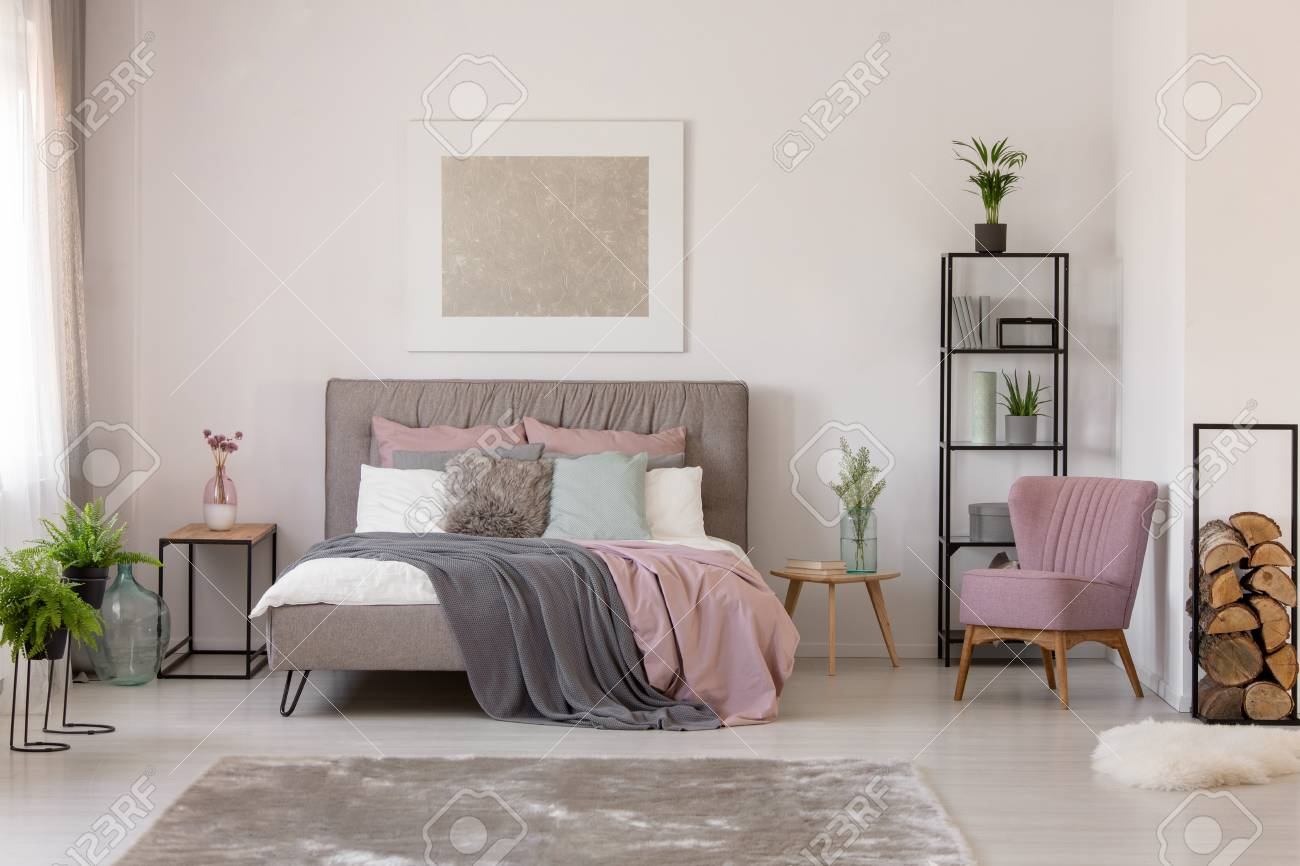 photo pink and grey sheets on bed next to armchair in bedroom interior with plants and poster real photo
