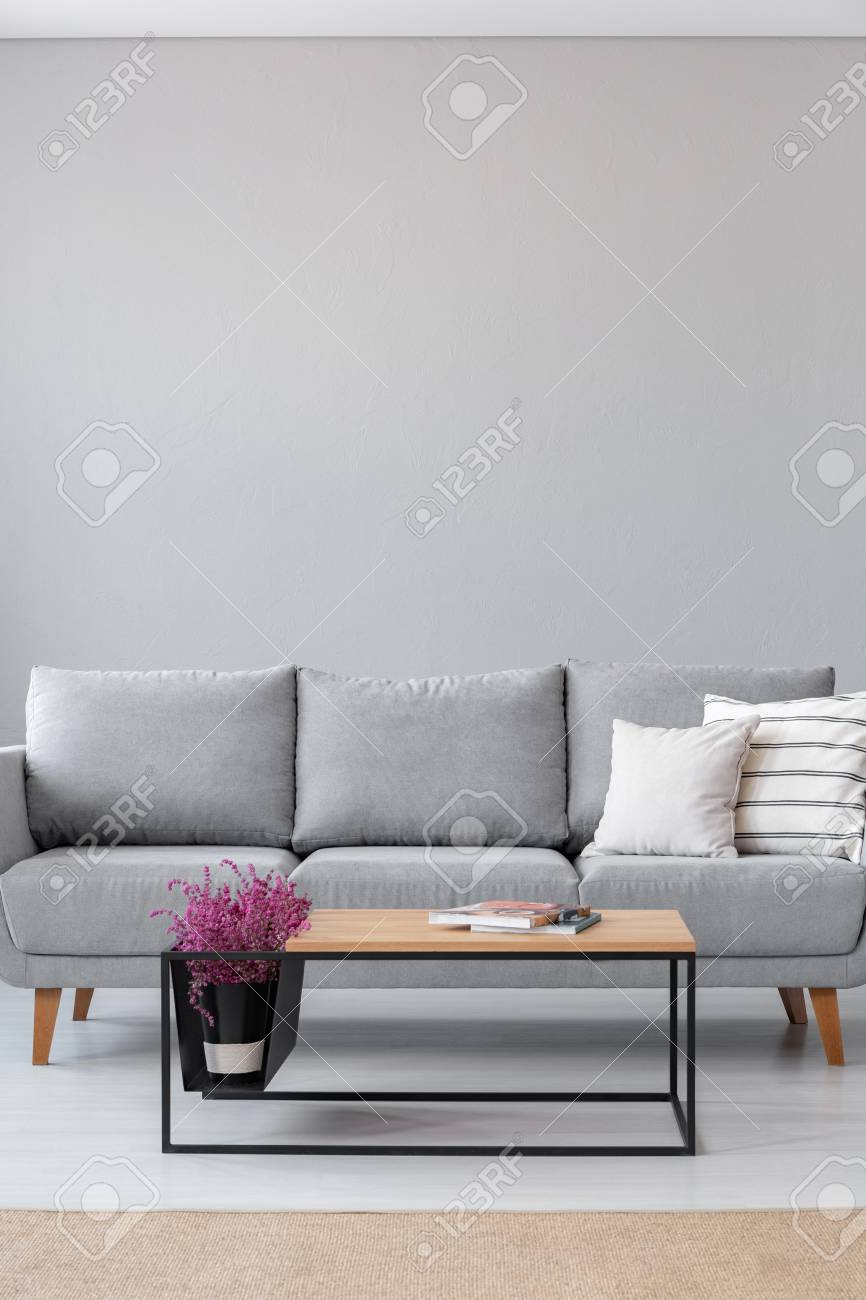 Stock Photo   Stylish Wooden Coffee Table With Magazines And Heather Next  To Grey Couch With White Pillows In Industrial Living Room Interior