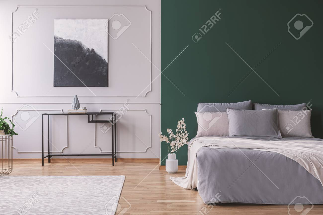 Dark green wall with copy space in stylish scandinavian bedroom interior with metal table black