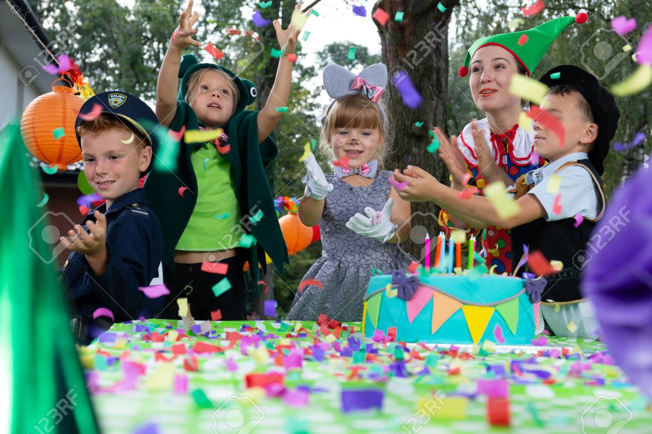 Smiling kids wearing in carnival costumes during colorful birthday party with cake - 111692503