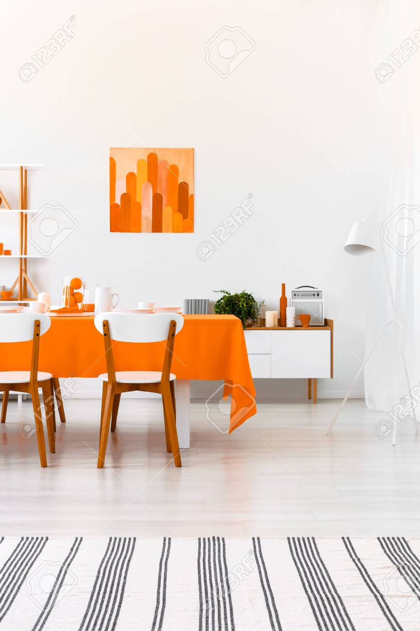 Striped carpet and poster in white dining room interior with..