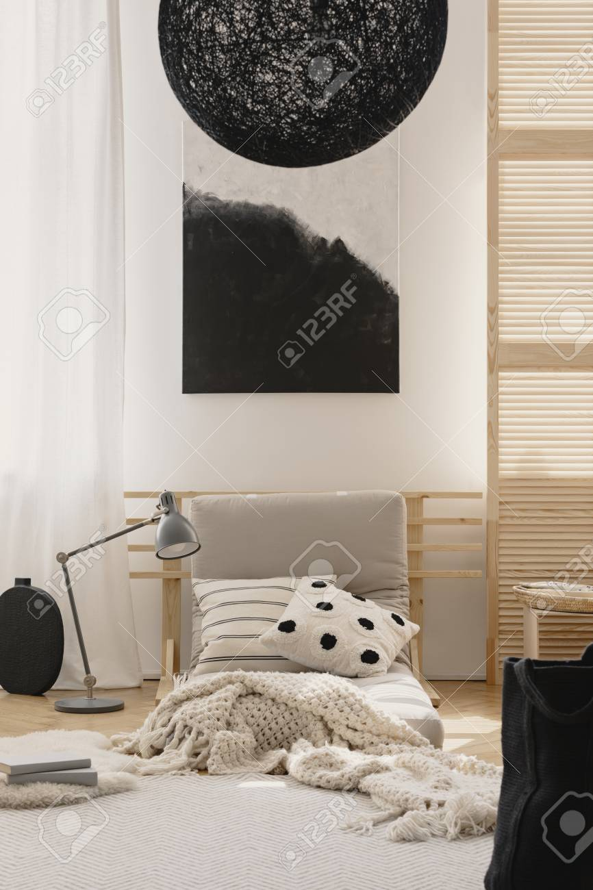 Stylish black chandelier and black and white abstract painting..