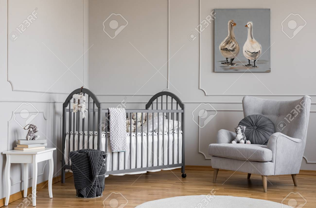 photo stylish grey baby room with wooden crib fortable armchair and white table with books real photo w