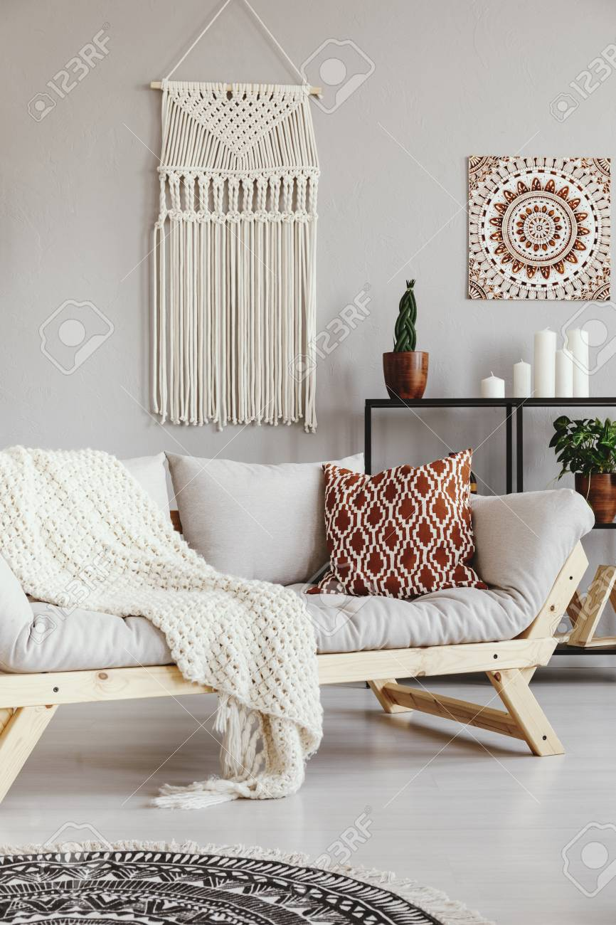 Patterned pillow and blanket on sofa in grey boho living room..