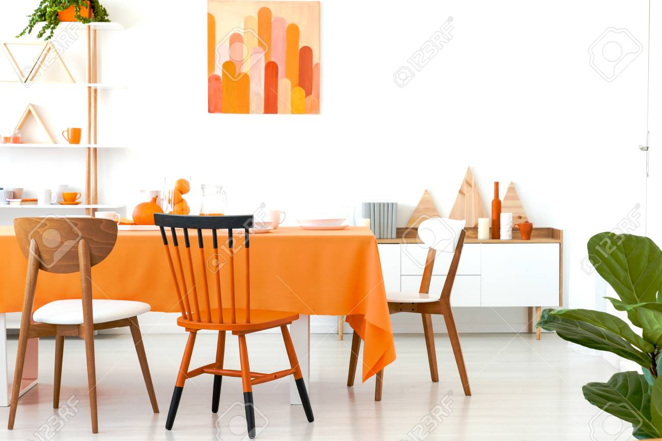 Three different chairs placed by the long dining table with orange tablecloth and dinnerware.White room interior with rack with decor, simple poster and cupboard with books - 112394840