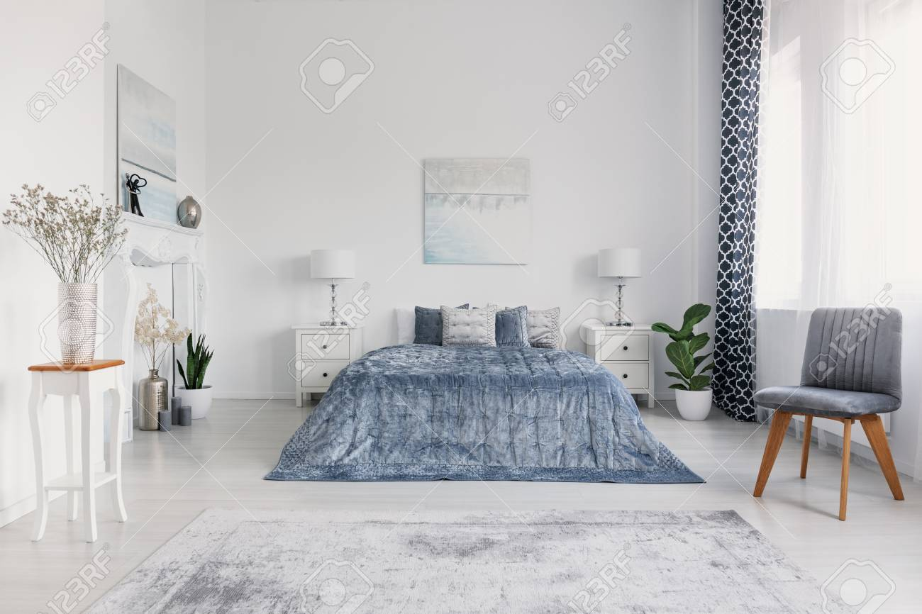 Grey chair next to blue bed in white bedroom interior with posters..