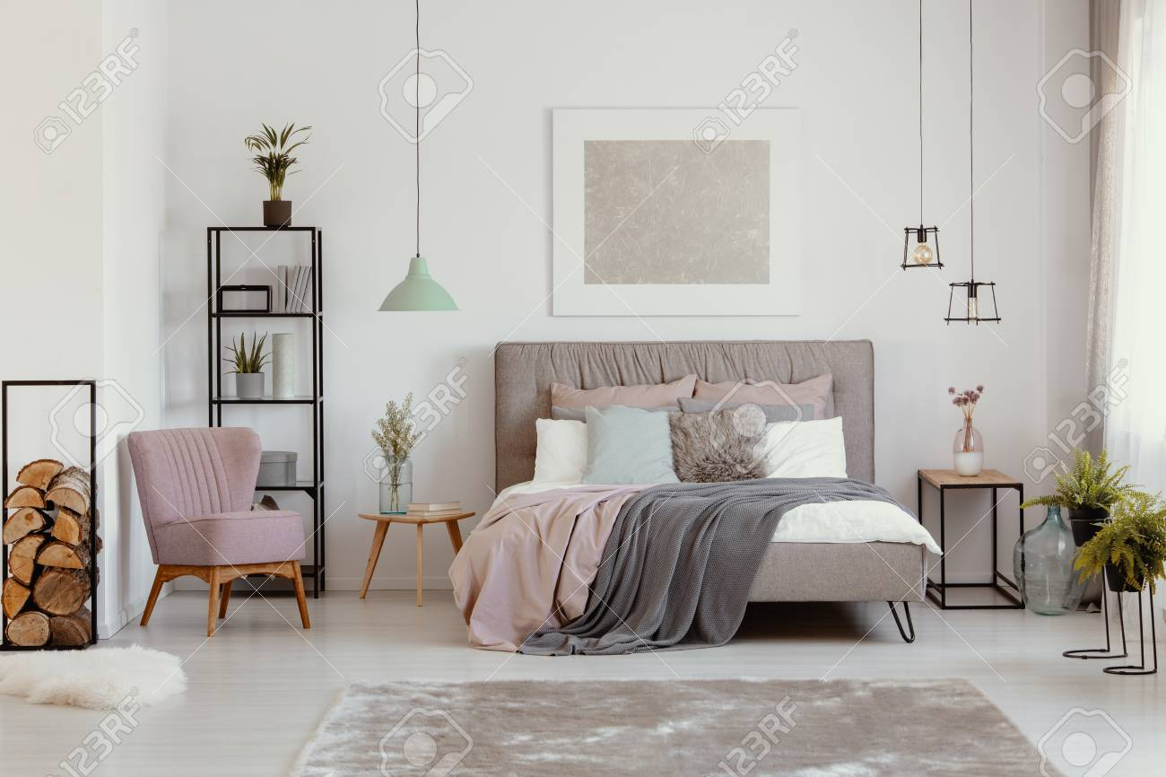 photo pink armchair next to grey bed with blanket in bedroom interior with poster and plants real photo