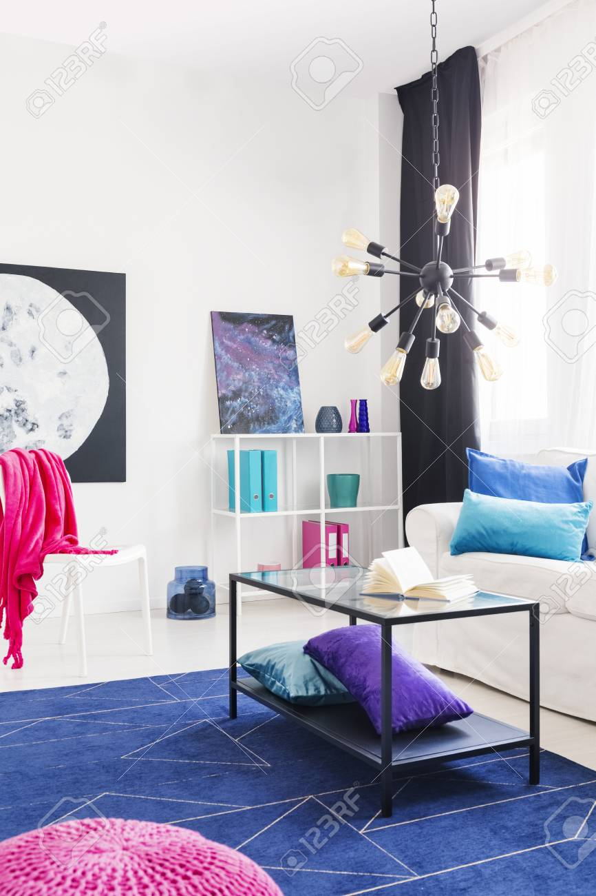 Table On Blue Carpet In Apartment Interior With White Couch And Pink