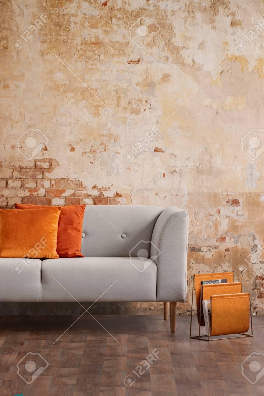 Orange Cushions On Grey Sofa Against Red Brick Wall In Modern Living